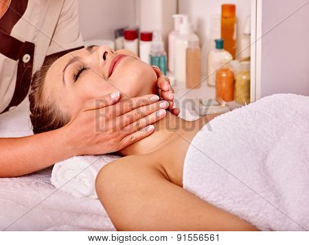 Young woman looking up getting facial  massage in beauty spa.