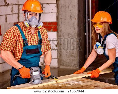 Man and woman in builder helmet working with electric planer.