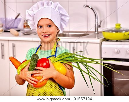 Child in cooking hat holding vegetable and onion at kitchen.