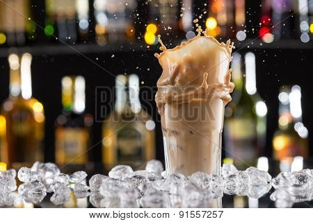 Cold coffee drink with ice, beans and splash, close-up.