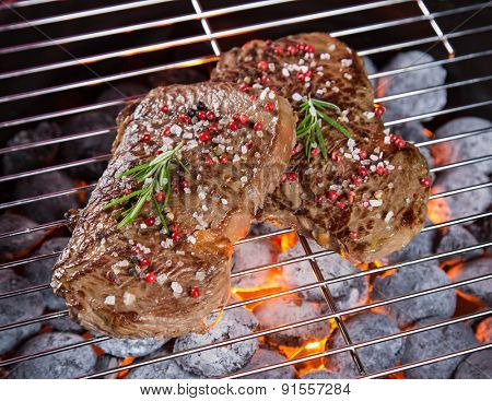 Delicious beef steaks on garden grill, close-up