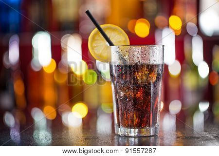 Glass of cola on bar desk, close-up.