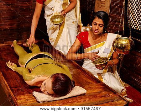 Young woman having green clay body Ayurveda spa massage.