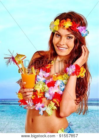Happy smiling woman in hawaii costume drinking   juice.