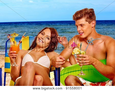 Couple with cocktail at  chair beach. Summer outdoor.