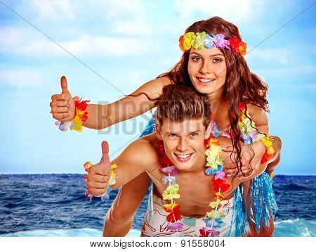 Couple showing thumb up on  beach. Summer outdoor.