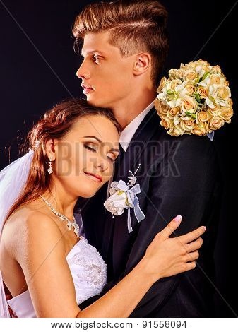 Bride with closed eyes and groom wearing wedding dress and costume.