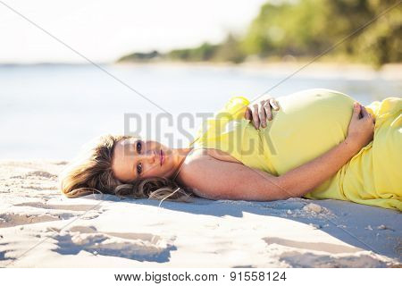 Pregnant woman with long hair in yellow dress lying down on the beach