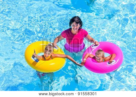 Family with children on beach ring in swimming pool. Summer outdoor.