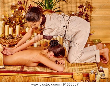 Young woman getting massage in bamboo spa. Two person.