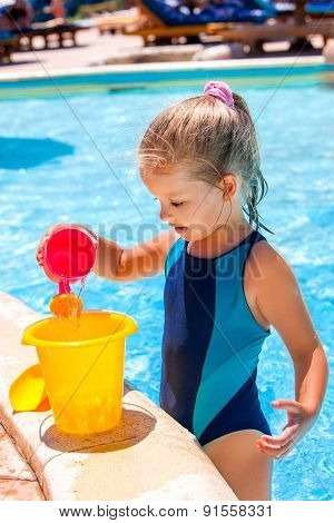 Child with bucket in swimming pool.  Little girl on summer outdoor.