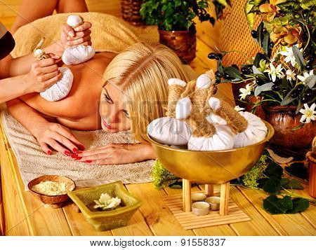 Blond woman getting massage hot herbal ball in tropical spa.