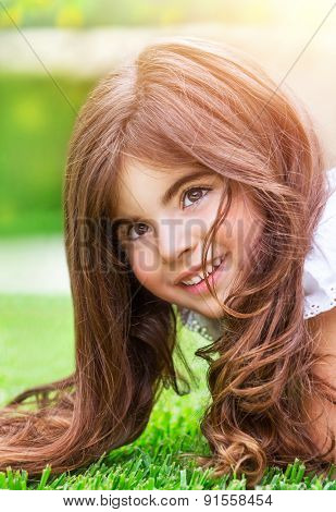 Closeup portrait of cute little girl lying down on fresh green grass field, having fun outdoors, relaxing in the park, happy childhood concept