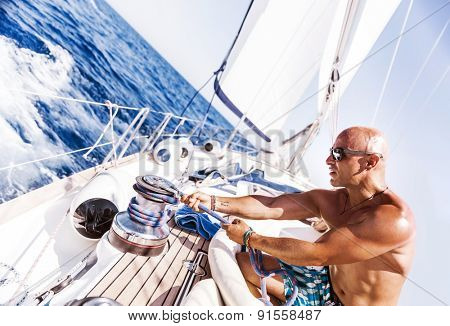 Handsome man working on sailboat, pulling rope, active summer vacation on water transport, having fun in the sea, enjoying water sport
