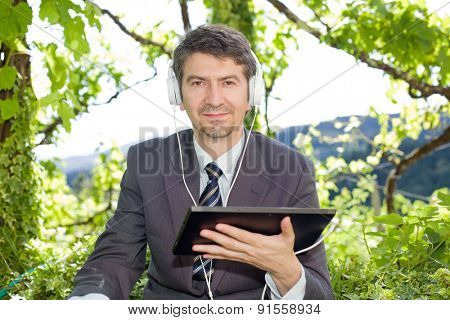 happy businessman with digital tablet and headphones, outdoors