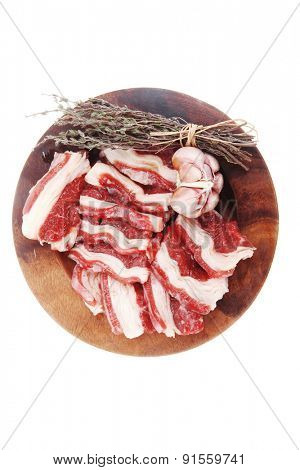 raw ribs with thyme and garlic on wooden isolated over white background