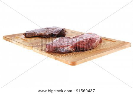 grilled and raw beef steak fillet meat on wooden board isolated over white background