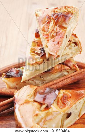 baked food : apple pies on wooden plate over table with cinnamon sticks . shallow dof