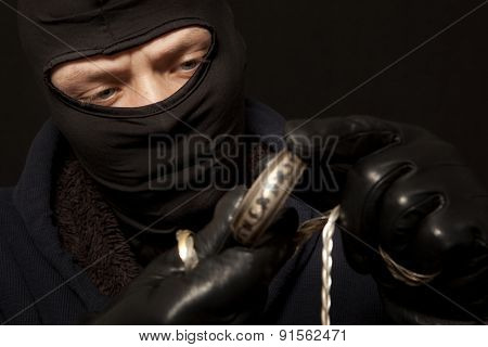 Thief. Man in black mask with a silver bracelet. Focus on thief