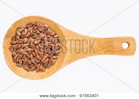 brown flax seeds on a small wooden spoon isolated on white with a clipping path