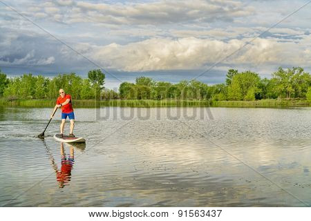 senior male on stand ups paddleboard - calm lake under stormy sky, springtime scenery in Colorado