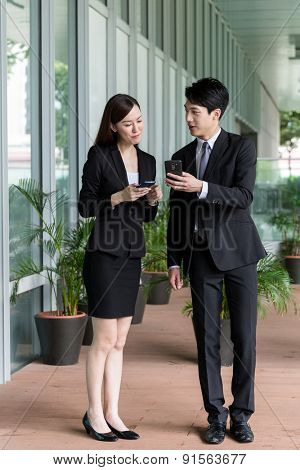 Asian businessman showing his cellphone with his colleague