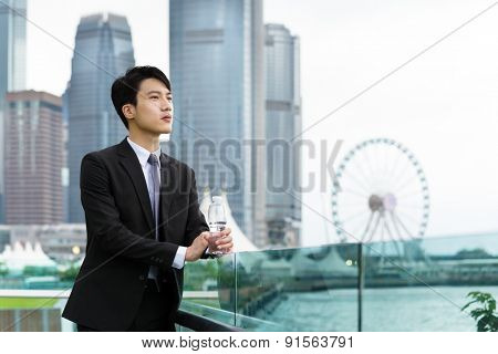 Asian businessman hold with water bottle at central district in Hong Kong