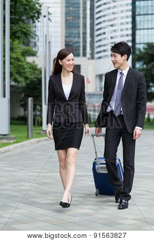 Businessman carry luggage for his business trip with his colleague