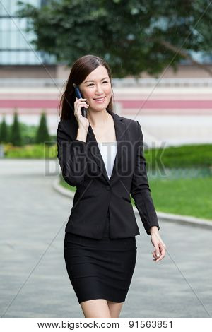 Businesswoman walking on the street and talking to cellphone