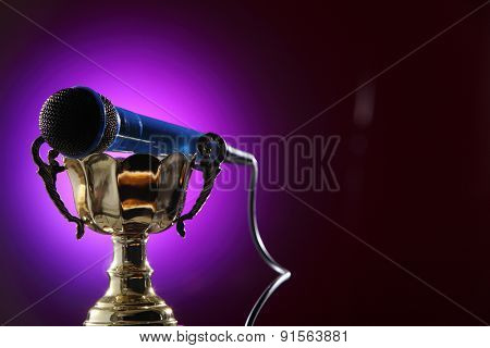 golden trophy  and microphone with purple background