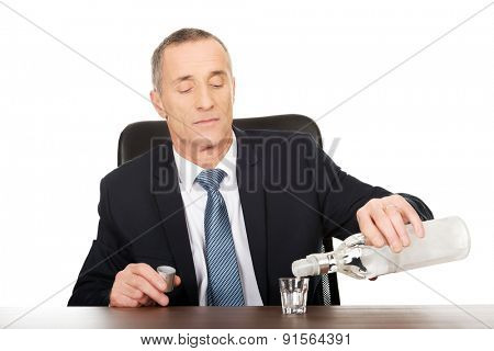 Businessman in office pouring vodka into a glass.