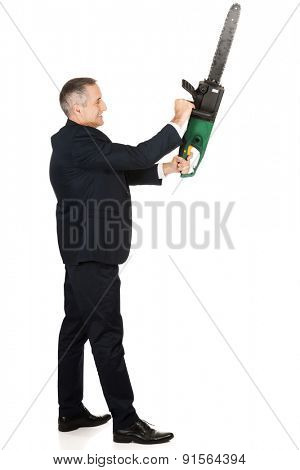 Furious mature businessman with chainsaw.