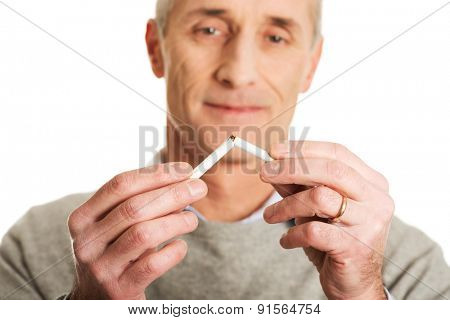 Portrait of mature man breaking cigarette.