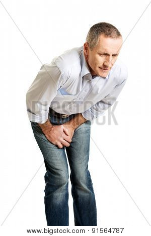 Embarassed man covering his painful crotch.