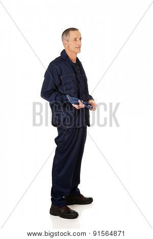 Full length side view plumber holding a wrench.