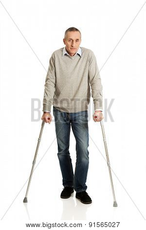 Full length mature man with crutches.