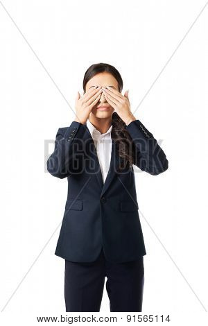 Full length young businesswoman covering eyes with hands.