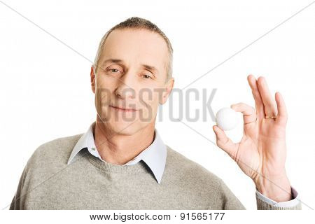 Portrait of mature man holding golf ball.