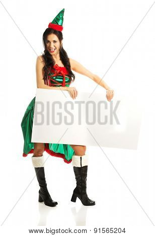 Full length woman wearing elf clothes holding white banner.