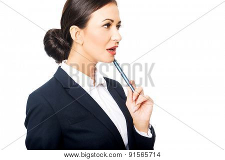 Portrait of businesswoman holding pen under chin.