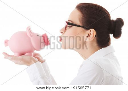 Woman giving a kiss to her piggybank.