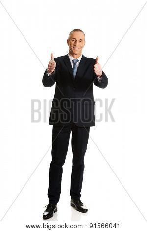 Full length businessman gesturing ok sign.
