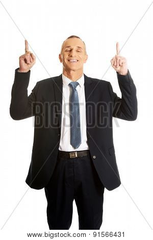 Businessman pointing upwards and smiling at camera.