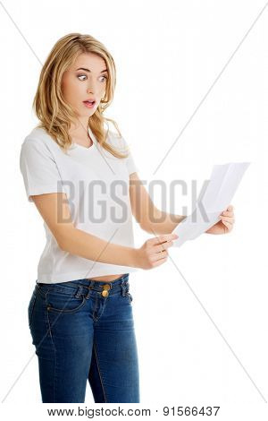 Surprised young woman reading some notes.