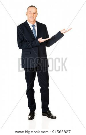 Full length businessman with welcome gesture.