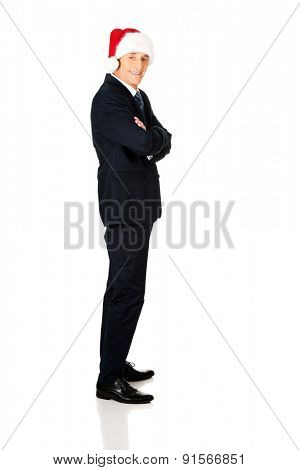 Side view businessman with folded arms wearing santa hat.