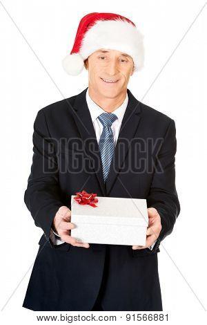 Portrait of a businessman wearing santa hat holding gift.