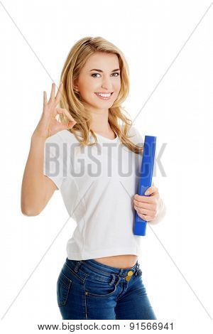 Young woman making ok sign holding binder.