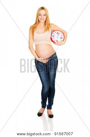 Happy pregnant woman with a big clock expecting baby