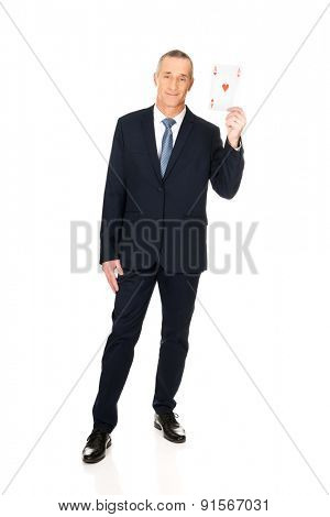 Full length elegant business man with red ace card.